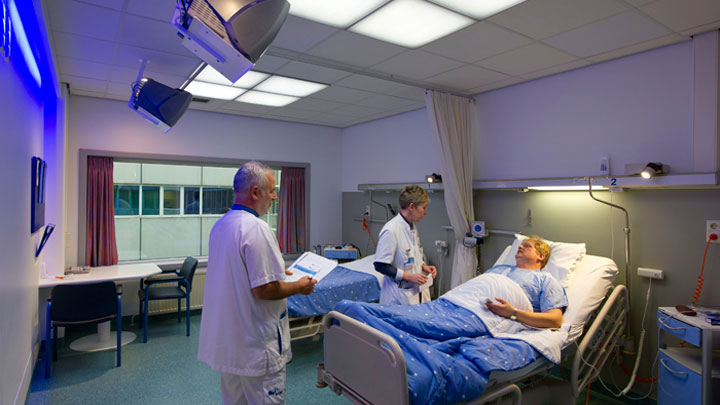 Doctors taking care of a patient in a room lighting up with Philips Healwell lighting system