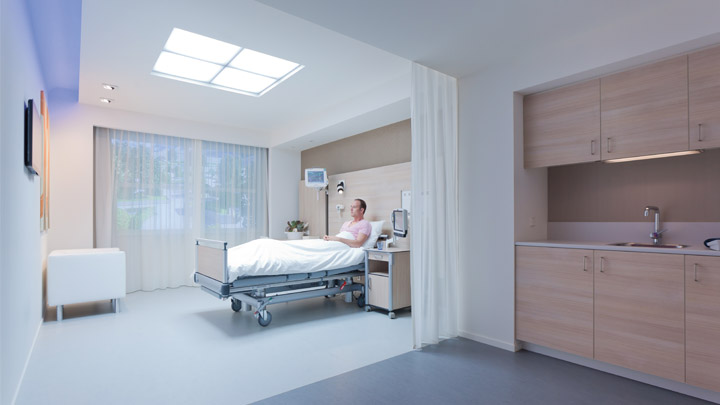 Nurse in softly lit room listing to patient's heart with patient - hospital lighting