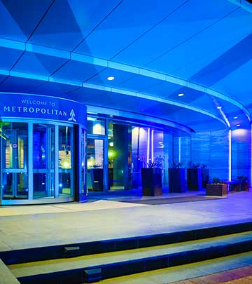 The doors to the Metropolitan building lit in blue corporate colours.